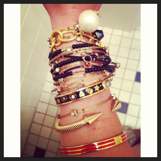 stacked bangles and bracelets in red black gold and pearl accents