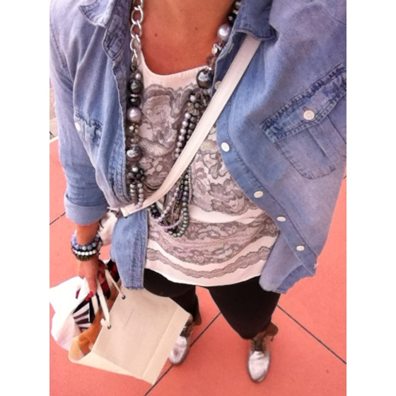 silver boots with black leggings, a graphic lace top, light denim, and a long necklace strand